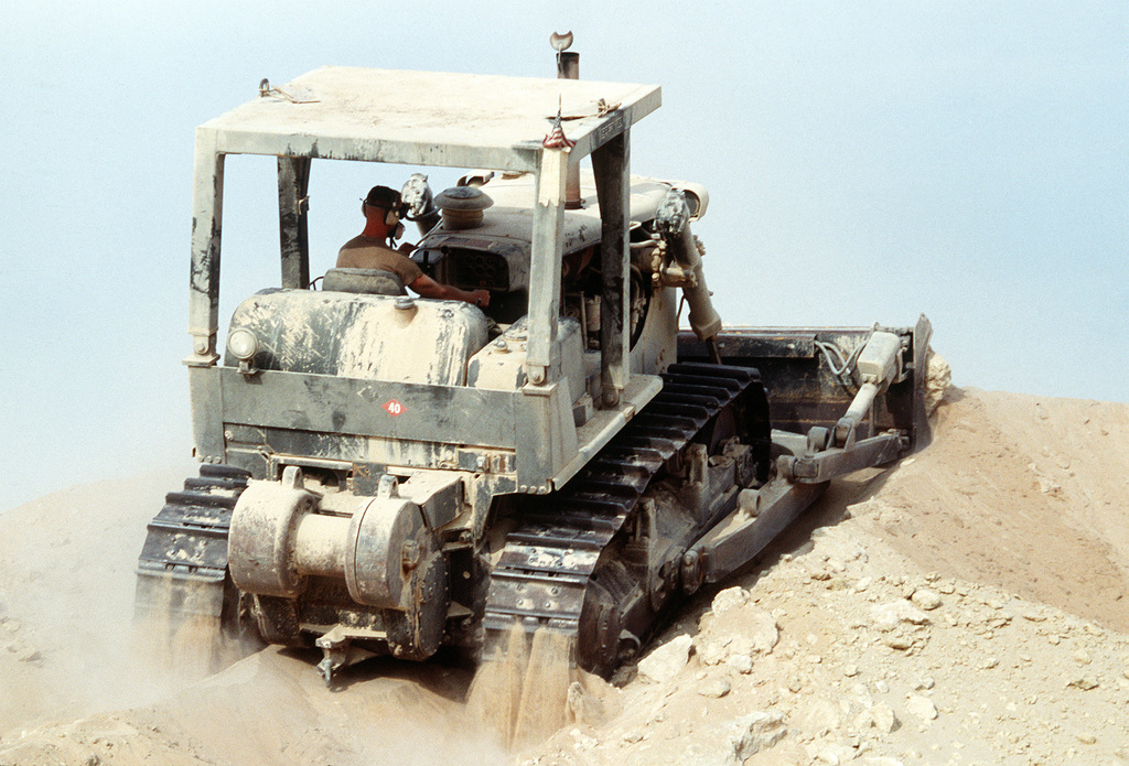 A Seabee from Naval Mobile Construction Battalion 40 (NMCB-40) operates a bulldozer while assisting in the construction of an ammunition supply point during Operation Desert Shield.
