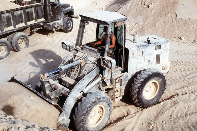 A Seabee from Naval Mobile Construction Battalion 40 (NMCB-40) operates a front loader while excavating a pit for an ammunition supply point during Operation Desert Shield.