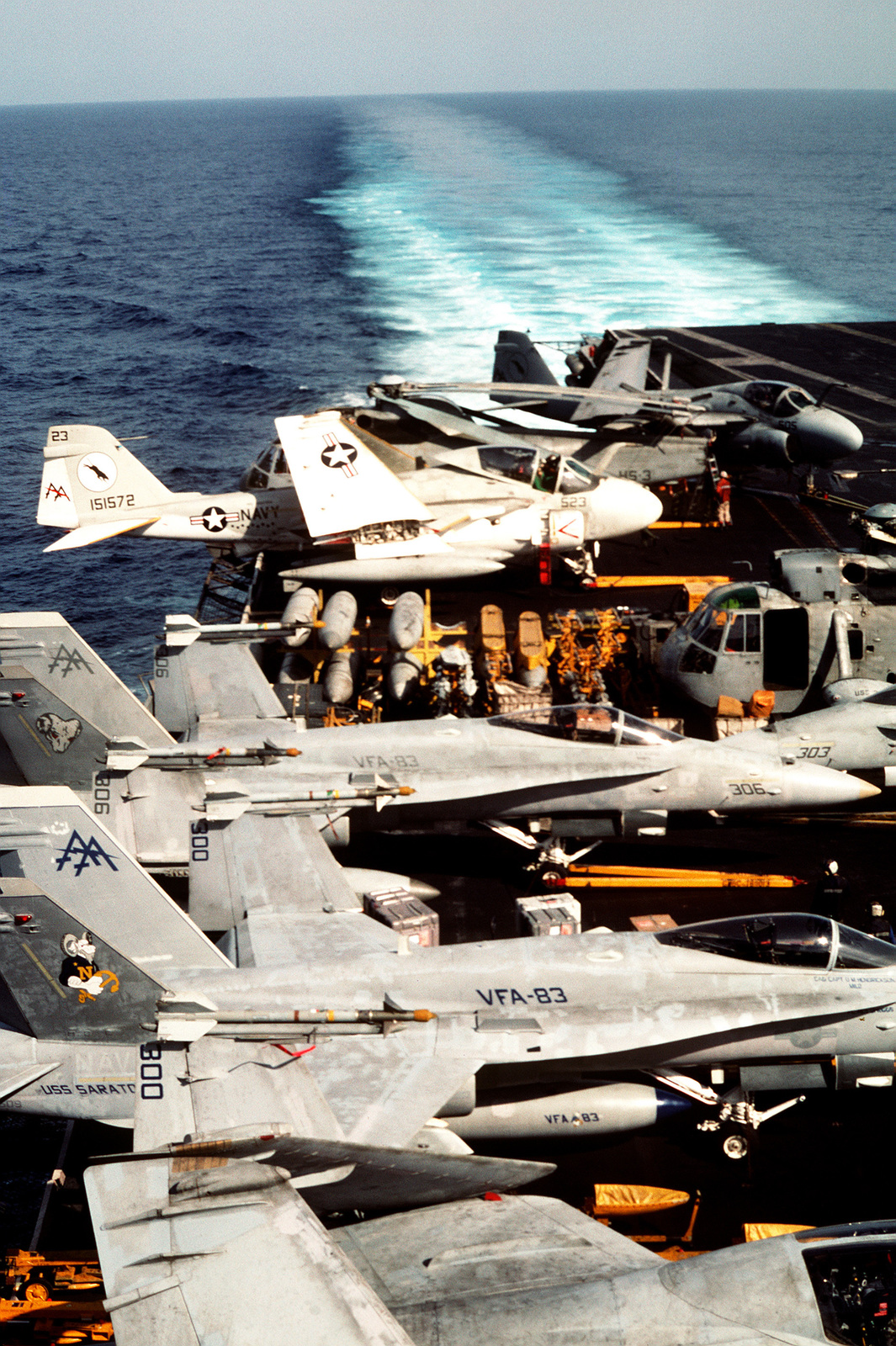 Strike Fighter Squadron 83 (VFA-83) F/A-18A Hornet aircraft armed with AIM-9 Sidewinder missiles, Helicopter Anti-submarine Squadron 3 (HS-3) SH-3H Sea King helicopters, and A-6E Intruder aircraft line the flight deck of the aircraft carrier USS SARATOGA (CV-60) as the vessel is underway in support of Operation Desert Shield