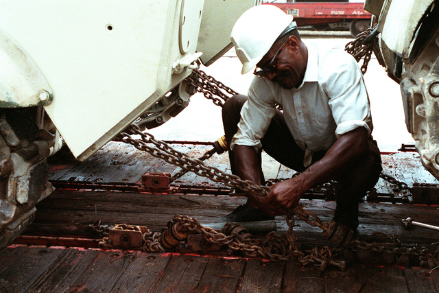 A workman loosens chains from a tracked vehicle at the rail yard prior to its unloading. The equipment is being prepared for transportation by ship to the Middle East in support of Operation Desert Shield