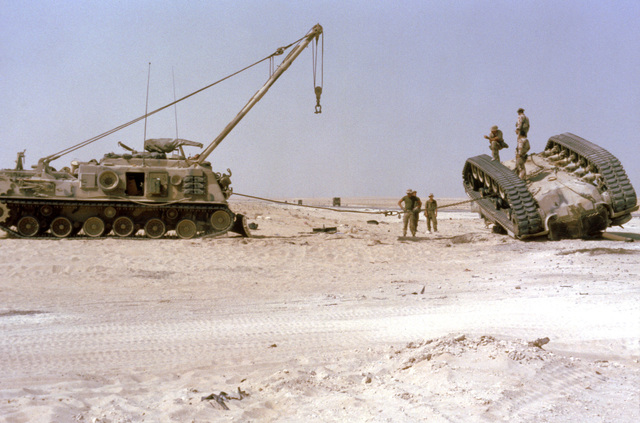 A Marine checks the cable linking an M-88A1 armored recovery vehicle (ARV) to an M-60 main battle tank before the ARV is used to upright the overturned vehicle. The exercise, part of Operation Desert Shield, simulates a possible battlefield situation