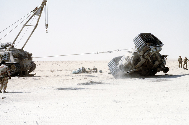 A Marine watches as an M-88A1 armored recovery vehicle uprights an overturned M-60 main battle tank. The exercise, part of Operation Desert Shield, simulates a possible battlefield situation