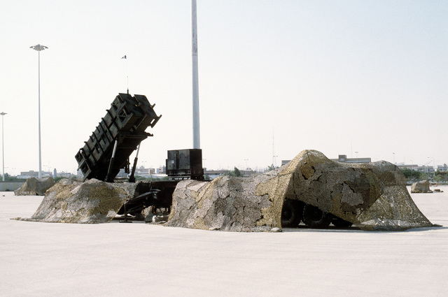 A partially camouflaged M-109 launching station for the MIM-104 Patriot missile stands ready for use during Operation Desert Shield