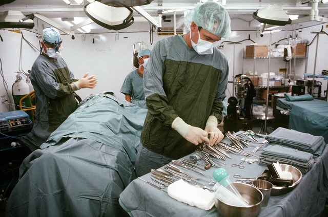 An assistant gets a pair of forceps for the doctor as a surgical team corrects a service member's deviated septum in a Fleet Hospital Five operating room during Operation Desert Storm