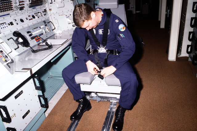 An officer secures himself into the Model 1101 missile crew member chair, developed by AMI Industries, as he sits at the control panel inside a Minuteman III intercontinental ballistic missile silo