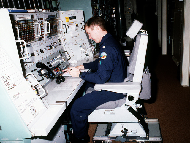 An officer tests the newly created model 1101 missile crew member chair, developed by AMI Industries, as he sits at the control panel inside a Minuteman III intercontinental ballistic missile silo