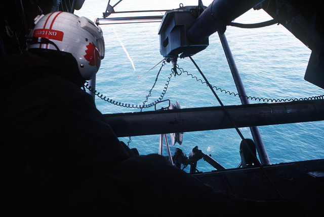 Aviation Machinist's Mate/AIRMAN J. Gudino checks the rigging from inside a Helicopter Mine Countermeasures Squadron 14 (HM-14) MH-53E Sea Dragon helicopter as the aircraft tows the sonar device of the AQS-14 minehunting system during operations off the coast of Abu Dhabi, United Arab Emirates. The system is being used to locate inert mines planted by U.S. forces as part of a minehunting exercise during Operation Desert Shield