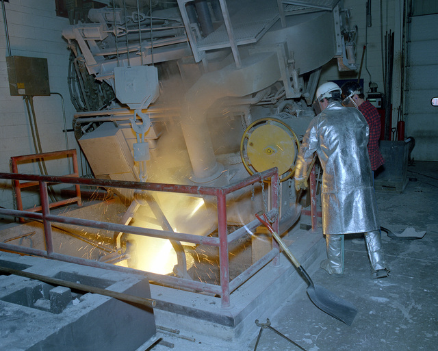 Everett Olive and Dan Zaiss, civilian employees at the arsenal, tap a three-ton arc furnace in Building 212W