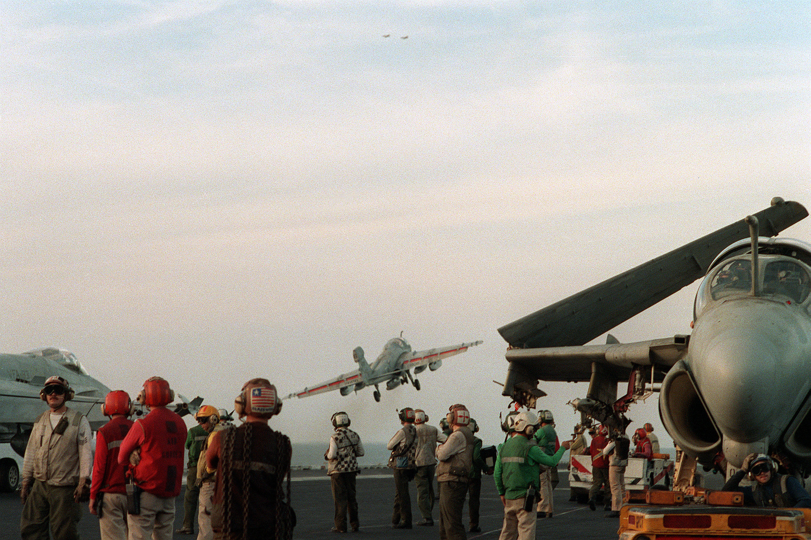 Flight deck crewmen aboard the aircraft carrier USS SARATOGA (CV-60) watch as an EA-6B Intruder aircraft is launched during Operation Desert Shield. An Attack Squadron 35 (VA-35) A-6E Intruder aircraft is at right