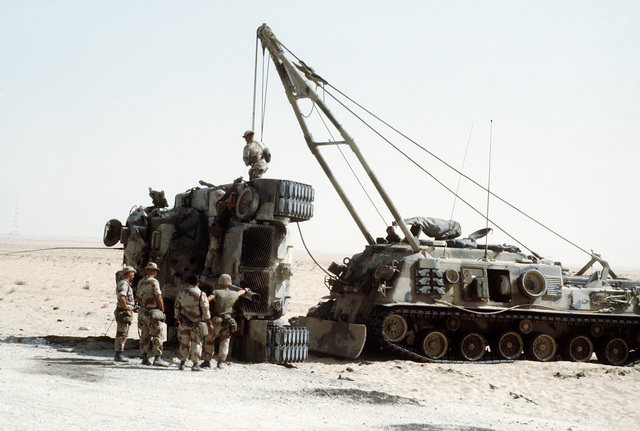 Marines gather around an M-60 main battle tank as an M-88A1 armored recovery vehicle is used to upright the overturned vehicle. The exercise, part of Operation Desert Shield, simulates a possible battlefield situation