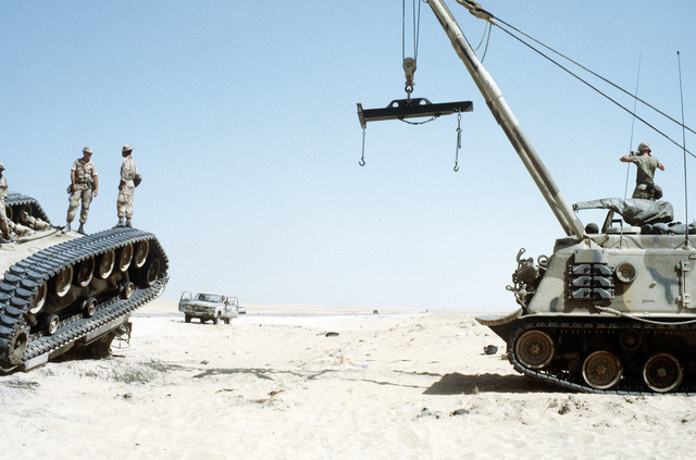 Marines stand atop an overturned M-60 main battle tank as the crane of an M-88A1 armored recovery vehicle is maneuvered into position to lift the tank. The exercise, part of Operation Desert Shield, simulates a possible battlefield situation