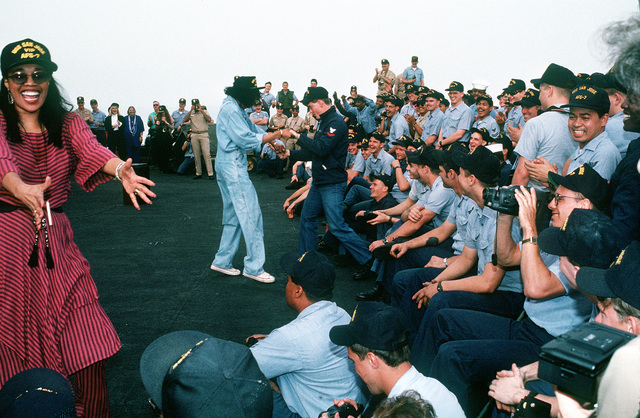 Two of the Pointer Sisters dance with some of the crewmen aboard the combat stores ship USS SAN JOSE (AFS-7) while performing in a United Service Organizations (USO) show during Operation Desert Shield