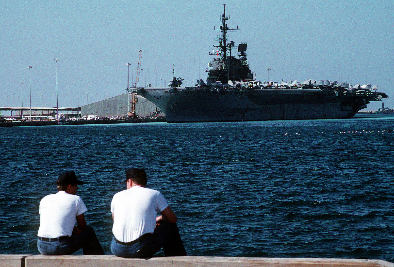 Two sailors talk on the pier as the aircraft carrier USS MIDWAY (CV-41) lies tied up in front of them during Operation Desert Shield