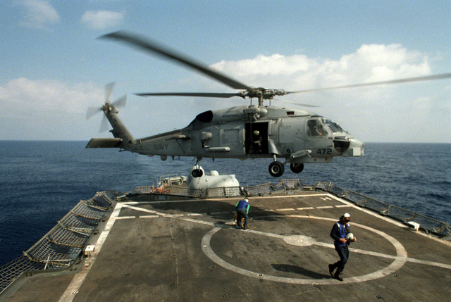A flight crewman aboard the guided missile cruiser USS BIDDLE (CG-34) disconnects a sling lowered from an SH-60B Sea Hawk helicopter. The BIDDLE is deployed in support of Operation Desert Shield