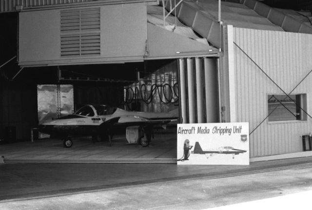 A T-37B Tweet aircraft is parked in a paint booth after receiving a fresh coat of paint