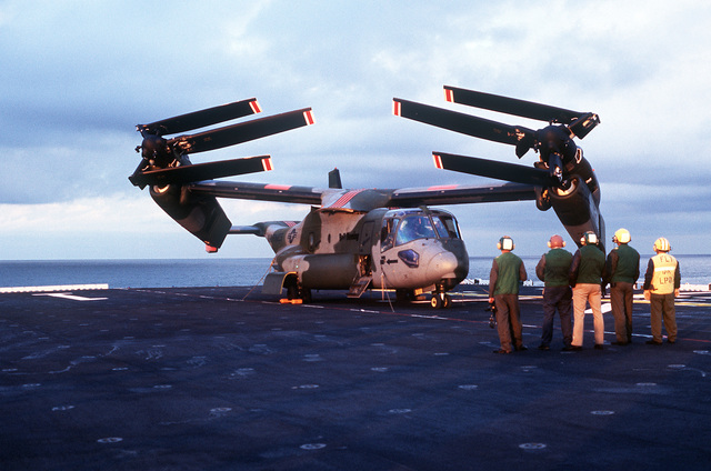 Flight deck personnel aboard the amphibious assault ship USS WASP (LHD-1) watch as a V-22A Osprey aircraft, its rotors folded inboard, rotates its wing 90 degrees into the shipboard stowage position. The aircraft is aboard the WASP for shipboard compatibility trials