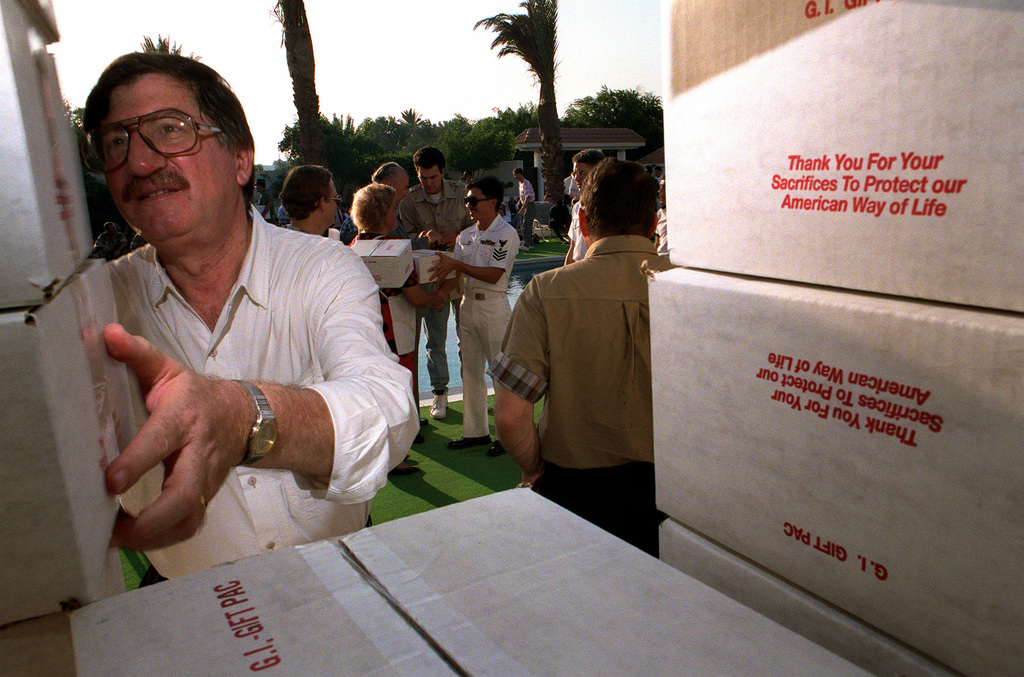 A volunteer from the United Service Organizations (USO) distribute gift packages to U.S. military personnel during a reception held at the residence of U.S. Ambassador to Bahrain Charles W. Hostler. Nearly 500 of the troops in Bahrain for Operation Desert Shield are attending the party, where they are also being treated to food and entertainment.
