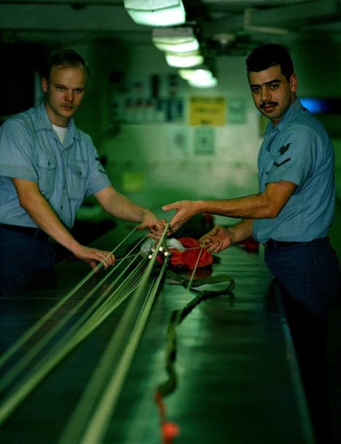 Aircrew Survival Equipmentman 3rd Class (PR3) Charles Landrum, left, and PR3 Erin Rusico lay out the shroud lines of a parachute they are repacking aboard the aircraft carrier USS JOHN F. KENNEDY (CV-67). The KENNEDY is deployed to the Red Sea in support of Operation Desert Shield