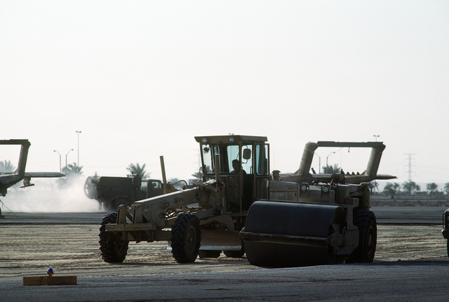 Members of a U.S. Navy construction battalion use a John Deere 670 motor grader to construct a runway during Operation Desert Shield