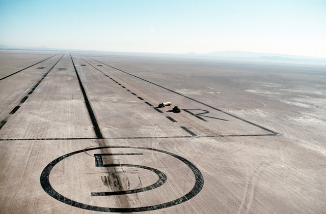 Maintenance vehicles cross the end of Runway 5 on Rogers Dry Lake. The dry lake, which covers more than 60 square miles, has 17 runways that provide ample landing space for test aircraft, space shuttles and aircraft unable to make a normal landing due to damage or equipment failure