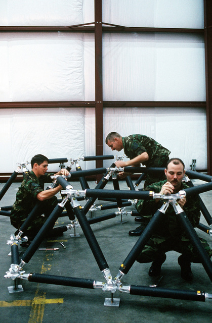 SSGT Jeffrey Dodson, left, TSGT Gary Cade, center, and SGT Steve Chabotte assemble a mirror bracket in an Air Force Astronautics Laboratory test facility. Laser research related to the Strategic Defense Initiative (SDI) is conducted by some of the laboratory's personnel