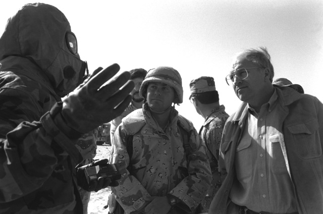 A Marine wearing Mission-Oriented Protective Posture response level 4 (MOPP-4) gear explains Nuclear, Biological, Chemical (NBC) defense methods to Secretary of Defense Richard B. Cheney during Operation Desert Shield