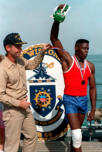 Captain D. S. Bill, Commanding Officer of the battleship USS WISCONSIN (BB 64), congratulates the winner of a match during a wrestling competition. The competition is part of the ship's holiday sports festival, which drew participants from the WISCONSIN and several other ships on station in the area of Operation DESERT SHIELD