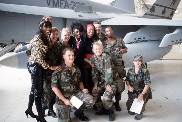 U.S. Air Force personnel pose with the Pointer Sisters after the Bob Hope Christmas Eve USO Show during Operation Desert Shield.