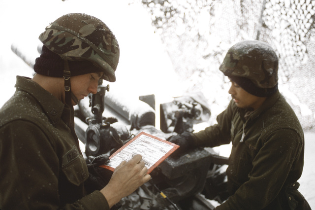 PFC Grady Pearson makes notes on a gunner's reference card as PFC Mati Puleola inspects the recoil mechanism on an M-101 105mm howitzer during CALFEX '90, a joint service, combined arms live-fire exercise. The soldiers belong to Btry. B, 5th Bn., 11th Field Arty