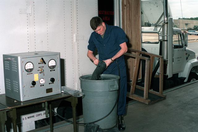 LCPL Peter T. Collings dips an inflated rubber glove into a container of water to check for leaks while working in the nuclear-biological-chemical (NBC) testing unit