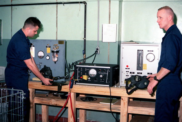 LCPL Rick L. Meyer, left, and CPL Steven F. Sparkman perform tests on M-17A1 field protective masks in the nuclear-biological-chemical (NBC) test unit