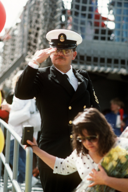 A chief petty officer returning from Operation Desert Storm salutes as he makes his way down the gangplank