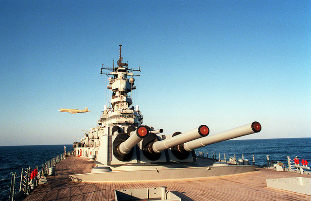 A close-up view of Mark 7 16-inch 50-caliber guns on the battleship USS WISCONSIN (BB-64) as the vessel is underway during Operation Desert Storm. A British BAe Nimrod aircraft flies near the vessel in the background.