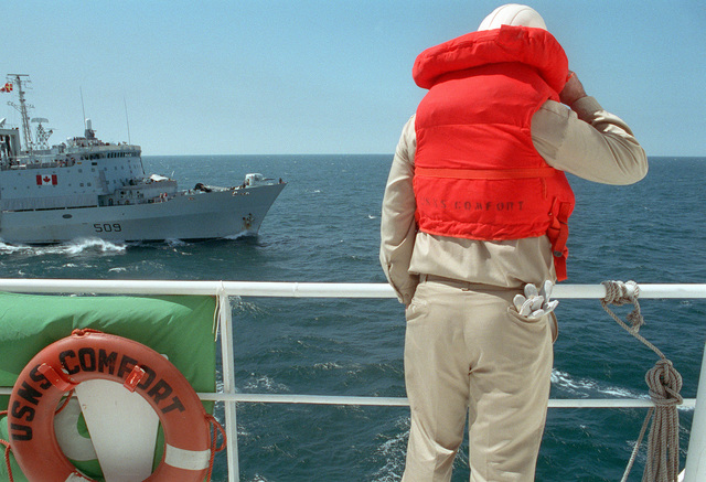 A crew member watches from the railing of the hospital ship USNS COMFORT (T-AH-20) as the Canadian operational support ship HMCS PROTECTEUR (AOR-509) approaches to take part in underway replenishment operations. Both vessels are deployed to the Persian Gulf during Operation Desert Storm