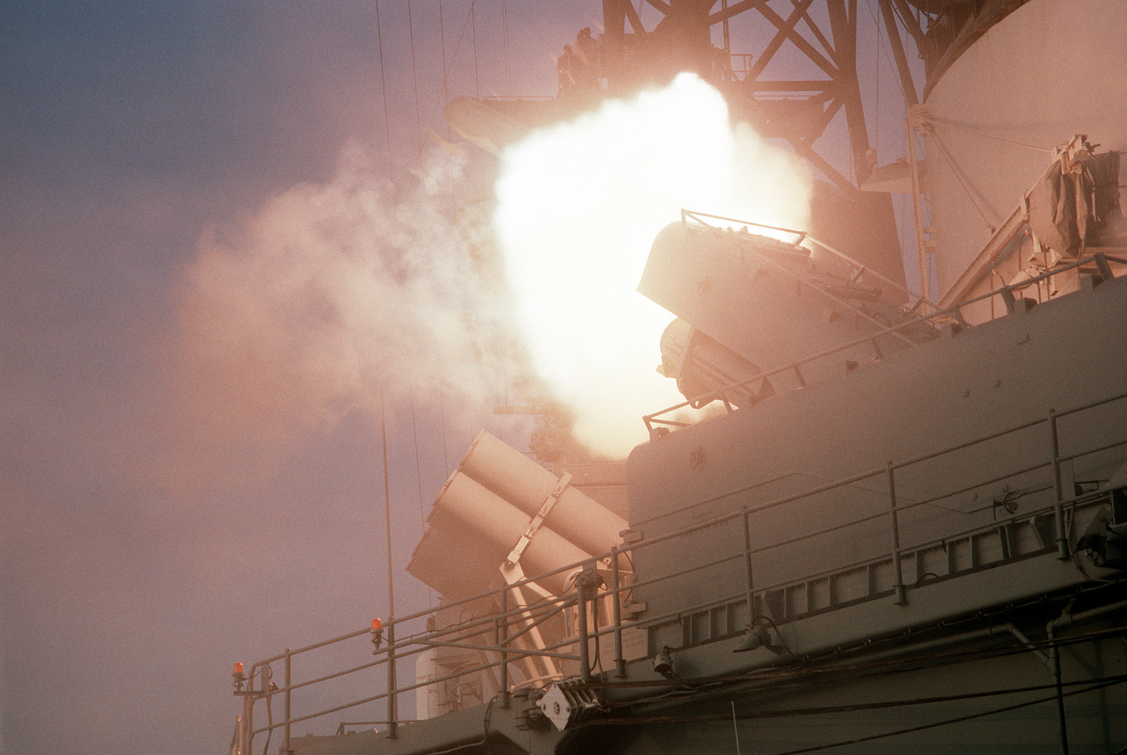 A fireball illuminates the upper decks of the battleship USS WISCONSIN (BB-64) as a BGM-109 Tomahawk land-attack missile is launched during Operation Desert Storm