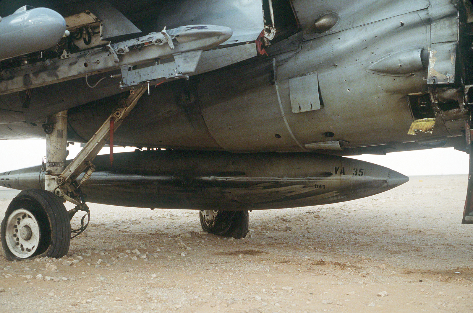 A fuel tank and the undercarriage of an A-6E Intruder attack aircraft from Attack Squadron 35 (VA-35), deployed from the aircraft carrier USS SARATOGA (CV-60), shows battle damage from a mission at the start of Operation Desert Storm.