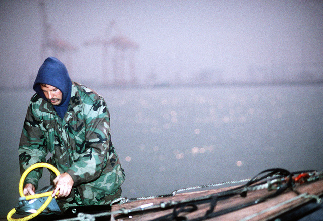 A member of an explosive ordnance disposal (EOD) stows a piece of equipment on the pier. U.S. and coalition EOD units are clearing mines and other ordnance from Kuwait's harbors following Operation Desert Storm