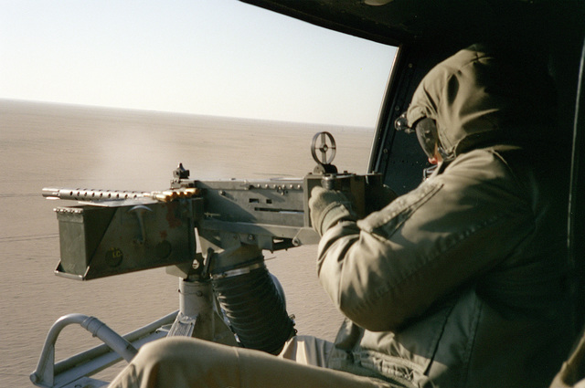 A member of Marine Light Helicopter Squadron 767 (HML-767) fires a .50-caliber M-2 machine gun from the door of a UH-1N Iroquois helicopter during during Operation DESERT STORM