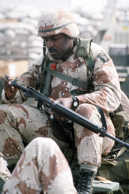 A member of the 101st Airborne Division cleans an M-16A2 rifle while waiting for transportation to his duty station at the start of Operation Desert Storm.