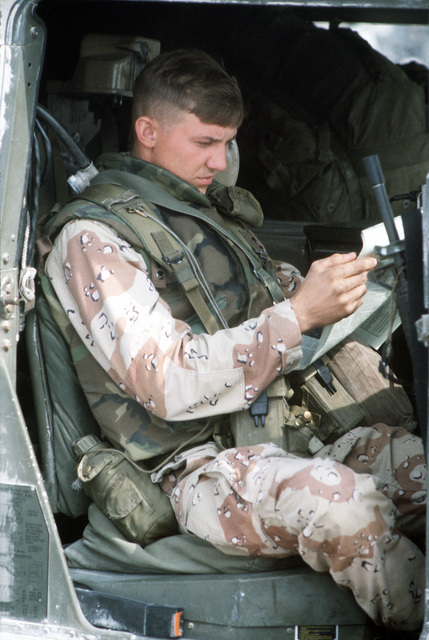 A member of the 101st Airborne Division reads the newspaper while waiting for transportation to his duty station at the start of Operation Desert Storm.