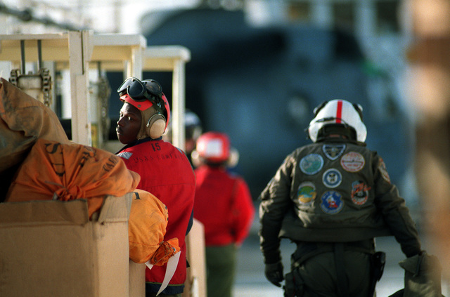 A pilot walks toward his SH-3 Sea King helicopter after delivering supplies aboard the hospital ship USNS COMFORT (T-AH-20) while the vessel is deployed to the Persian Gulf during Operation Desert Storm