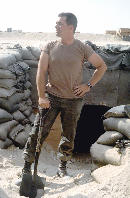A Seabee from Naval Mobile Construction Battalion 74 takes a break from shoveling sand away from the opening to a bunker during Operation Desert Storm. Exact Date Shot Unknown
