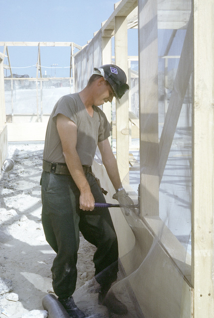 A Seabee of Naval Mobile Construction Battalion 74 attaches screening to a tent frame in a Marine camp which is being built during Operation Desert Storm. Exact Date Shot Unknown