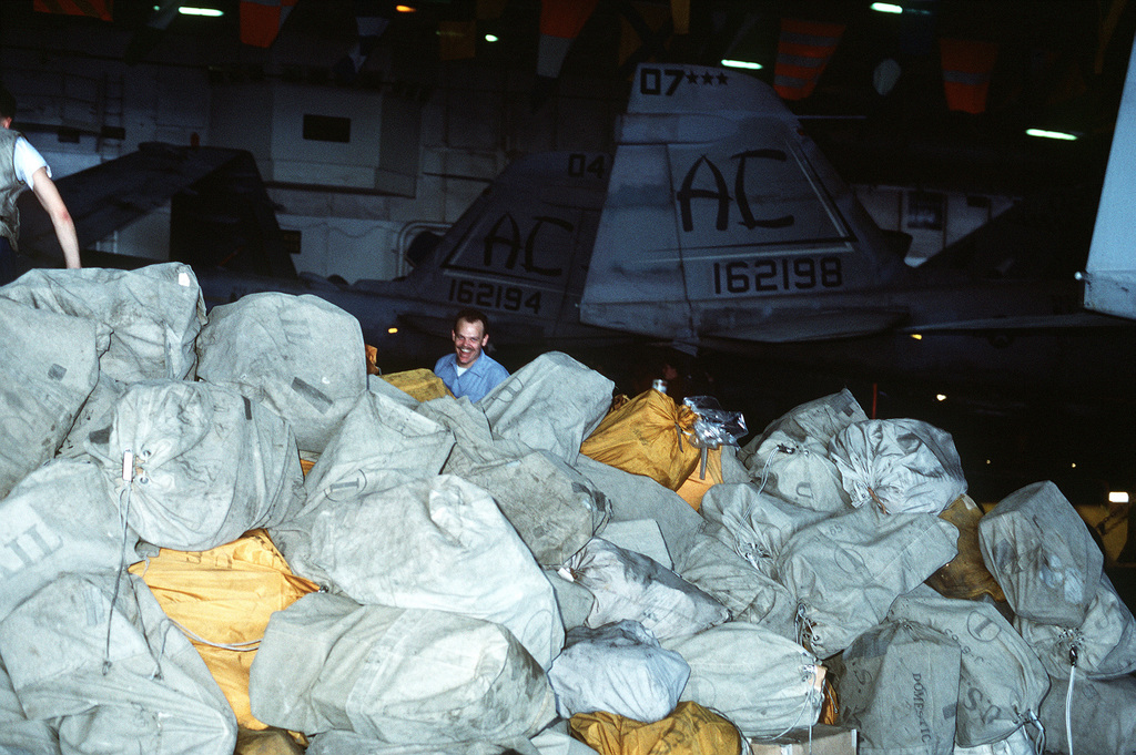 A smiling sailor stands behind a heap of mail bags on the hangar deck of the aircraft carrier USS JOHN F. KENNEDY (CV-67) during Operation Desert Shield. More than 40,000 pounds of mail was delivered in this one shipment