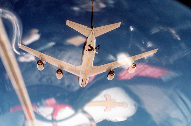 A view from the cockpit of a Fighter Squadron 32 (VF-32) F-14A Tomcat aircraft as it flies beneath a U.S. Air Force KC-135E Stratotanker aircraft prior to an in-flight refueling during Operation Desert Storm. VF-32 is based aboard the aircraft carrier USS JOHN F. KENNEDY (CV-67), which is on station in the Red Sea