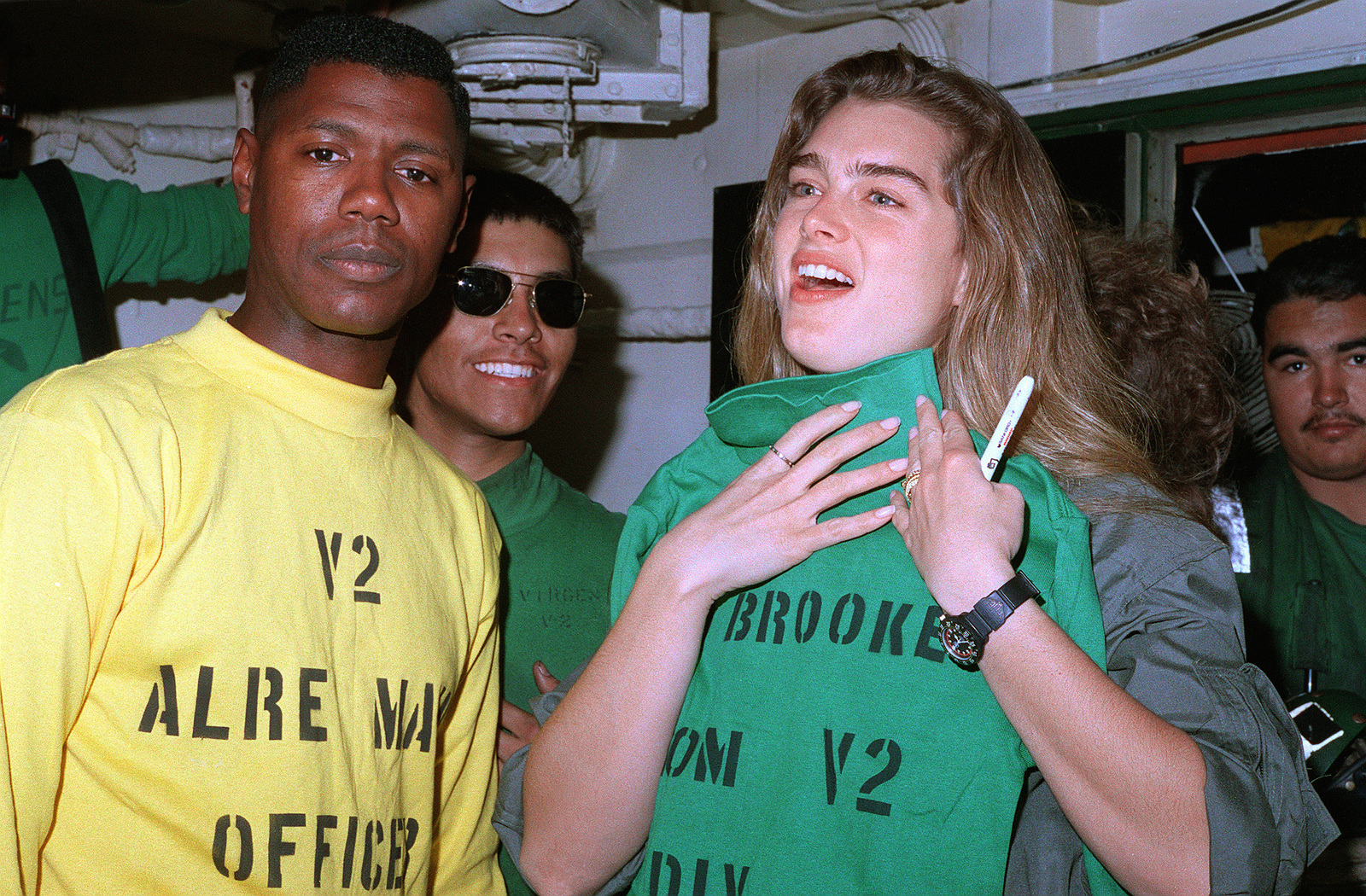 Actress Brooke Shields holds up a flight deck jersey presented to her by ENSIGN Richard Jones, the aircraft launching and recovery equipment (ALRE) maintenance officer aboard the aircraft carrier USS MIDWAY (CV-41). Shields' visit to the Midway is part of a tour sponsored by the United Service Organizations (USO). The MIDWAY is in the gulf to support Operation Desert Shield