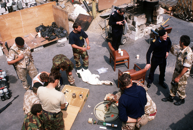 American, British and Australian explosive ordnance disposal (EOD) divers gather at their base camp after a day's work. U.S. and coalition EOD units are clearing mines and other ordnance from Kuwait's harbors following Operation Desert Storm