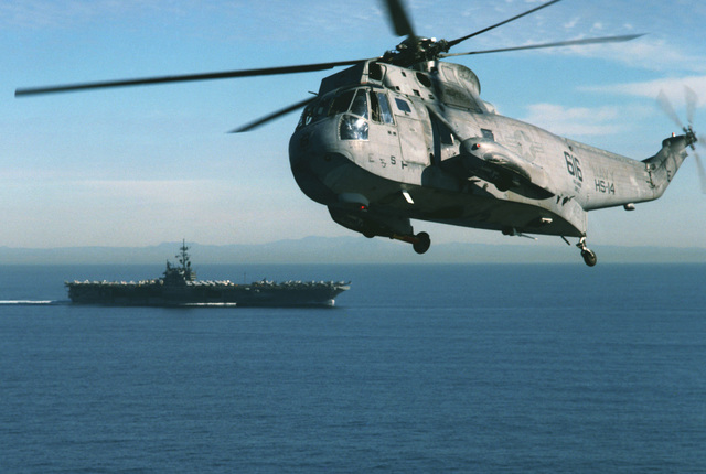 An aerial view of a US Navy (USN) SH-3H Sea King helicopter, Helicopter Anti-Submarine Squadron 14 (HELASRON HS-14), Chargers, with the USN Aircraft Carrier USS RANGER (CV 61) and the California coastline in the background