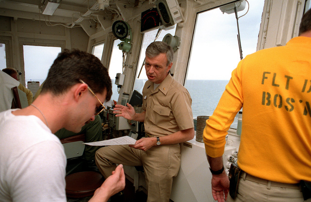 An officer instructs a crew member on the bridge of the hospital ship USNS COMFORT (T-AH-20) as the vessel is deployed to the Persian Gulf during Operation Desert Storm