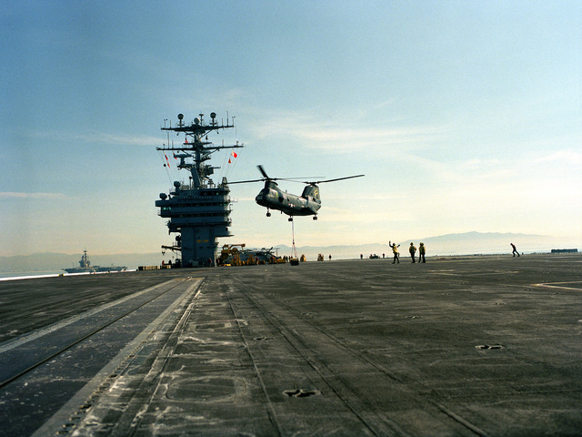An overall view of a US Navy (USN) CH-46D Sea Knight, Helicopter Combat Support Squadron 11 (HC-11), Gunbearers, Naval Air Station North Island (NASNI), delivering a pallet of MK-82 casing onto the deck of the USN Nimitz Class Aircraft Carrier USS ABRAHAM LINCOLN (CVN 72) during a Vertical Replenishment (VERTREP) mission
